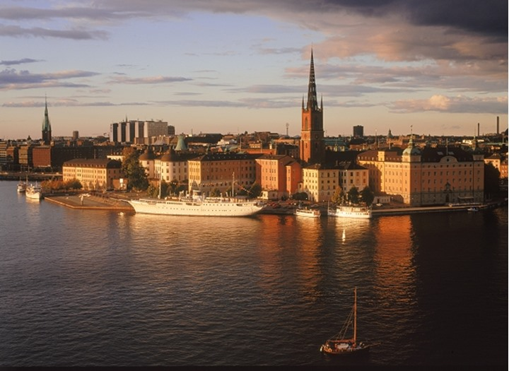 Tyn Church steeple in Old Town and Riddarholmen Island reflecting off Riddarfjarden waters in Stockholm