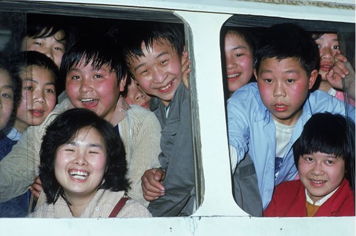 School children looking out bus windows near Guilin in China
