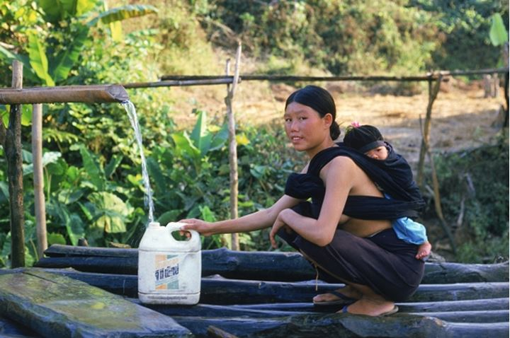 Hill Tribe woman from Lisu village filling plastic container with water with baby on her back in Northern Thailand