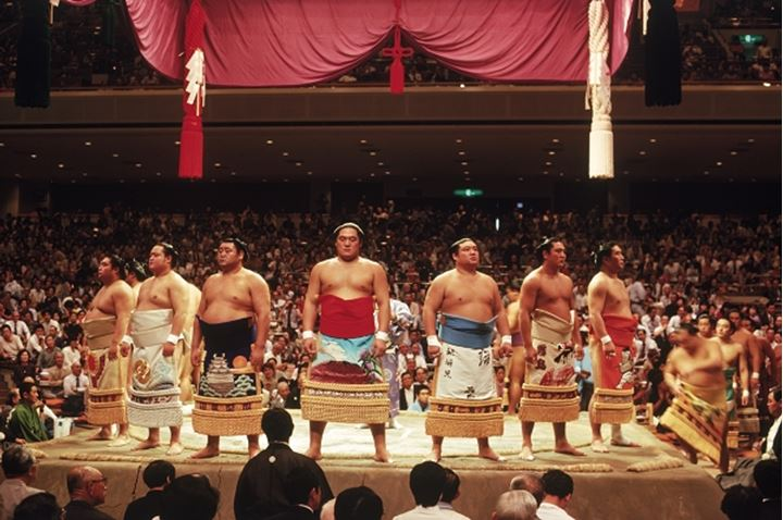 Pre fight sumo wrestling ceremony of  competitors parading around ring or dohyo in traditional costume