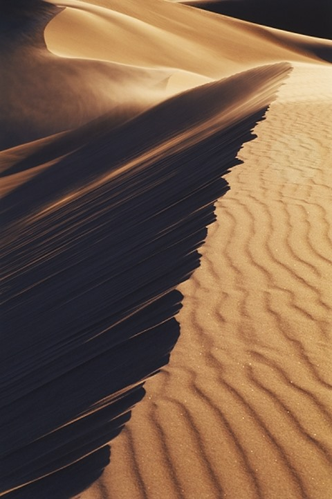 Wind creating waves across sand dune in low light