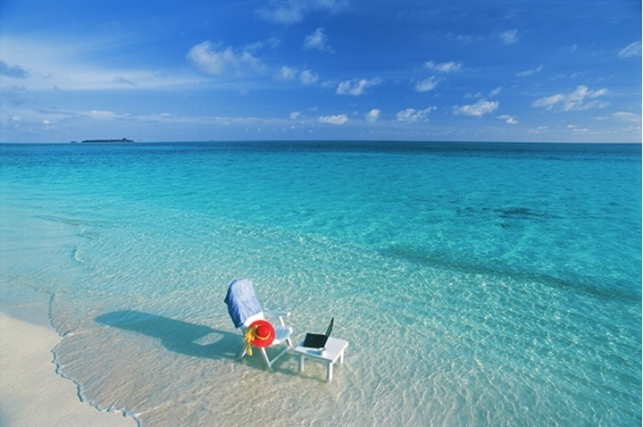 Chair and table with laptop and cellphone on beach in Maldives representing working holidays