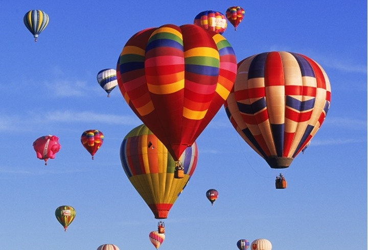 Colorful floating balls carrying baskets of people through clear blue skies