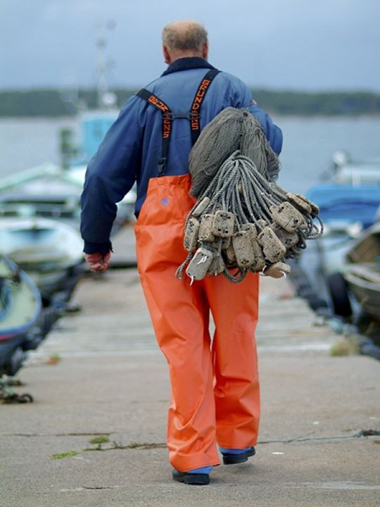 Rear view of a man walking with ropes and buoys