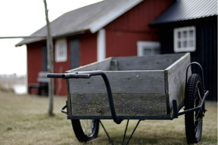A cart with wheels and red cottage