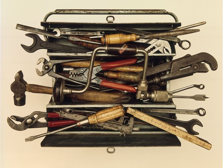 An open toolbox with tools flowing out of it
