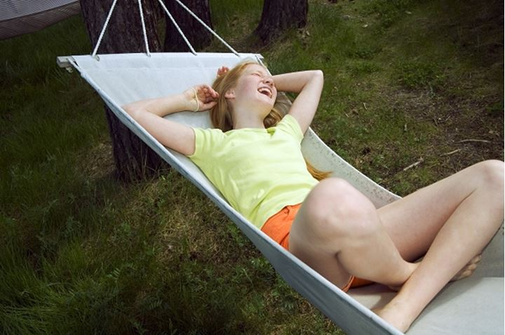 High angle view of a teenage girl lying in a hammock, Sweden.