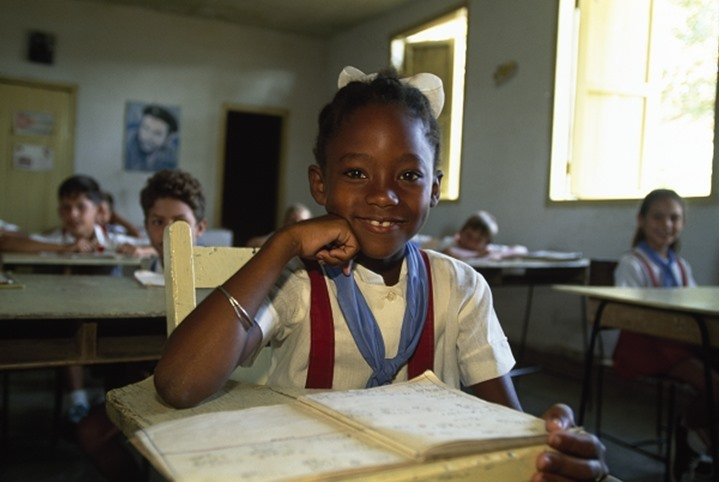 An arfican girl smiling at camera while sitting on chair in a classroom