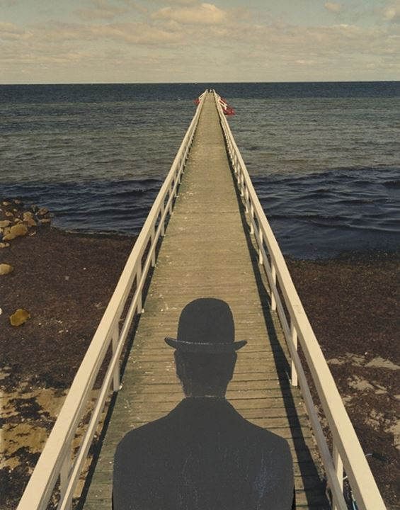 A landing by a seashore, a man with a hat by the end of it