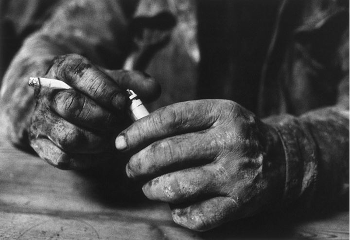 Close up of messy hands holding cigarette and lighter