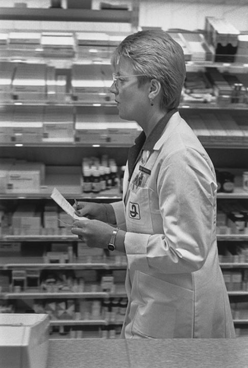 Side view of a pharmacist in dispensary