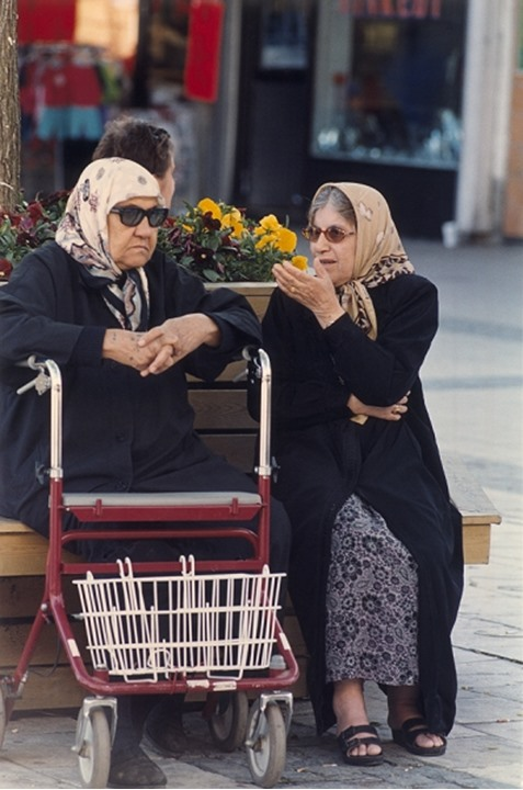 Front view of two elderly women talking whilst sitting outdoors