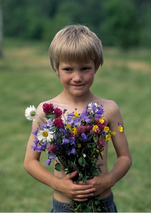 Boy holding a bunch of colourful flowers