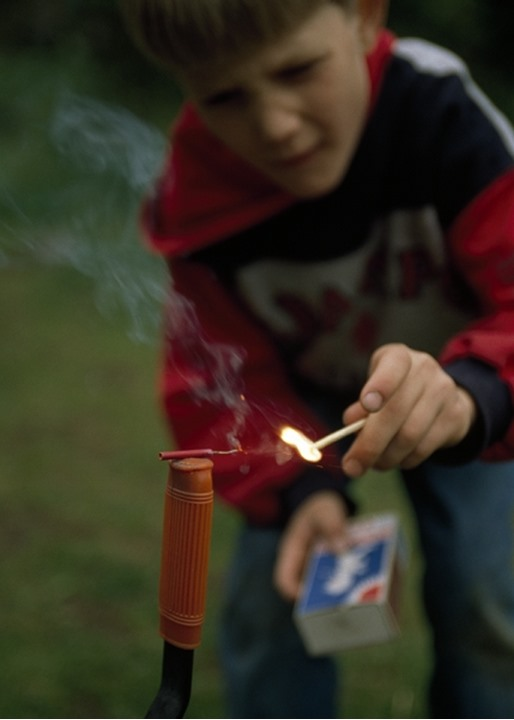 Child burning cracker with a lighted matchstick