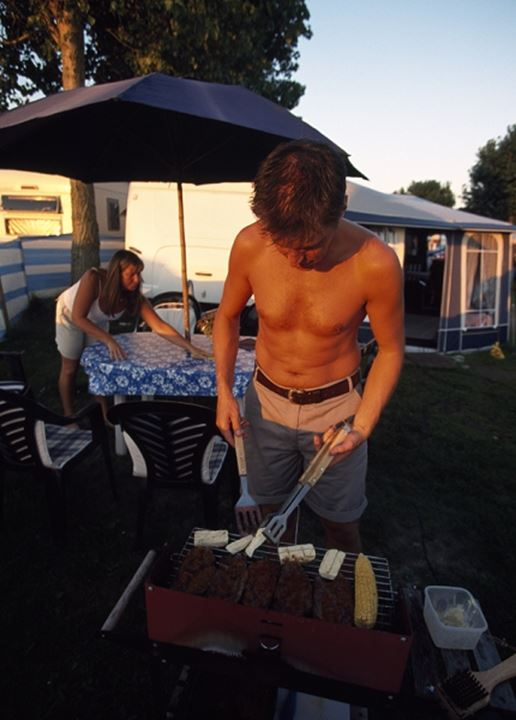 Man barbequing in the lawn,camping