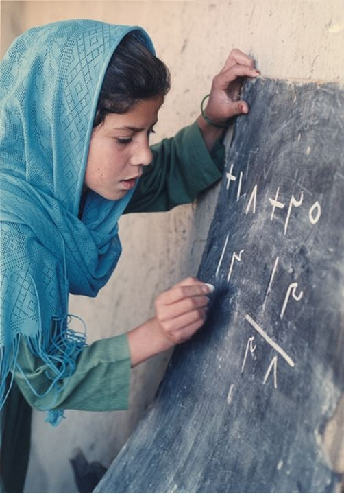 Side view of a girl writing on the blackboard, Afghanistan