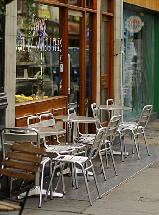 Empty chairs and table arranged at an outdoor cafe in London, England, Europe
