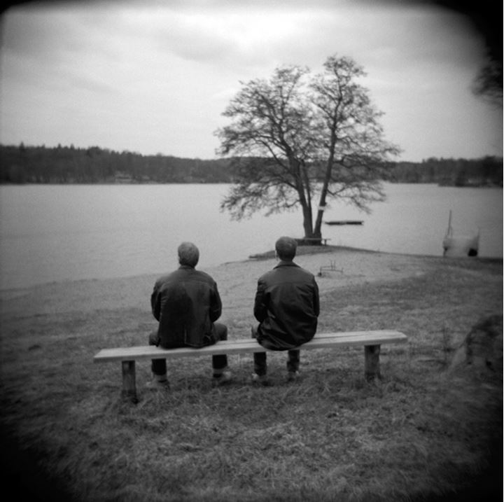 Two men sitting on a bench overlooking a lake, Sweden