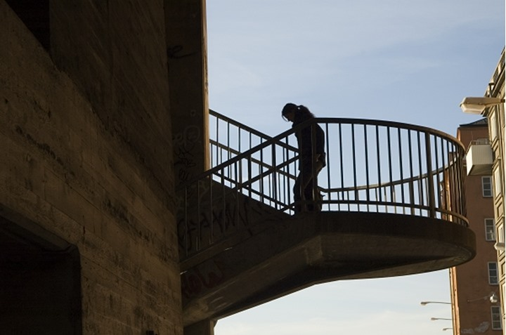 Side view of a silhouetted person descending through stairways