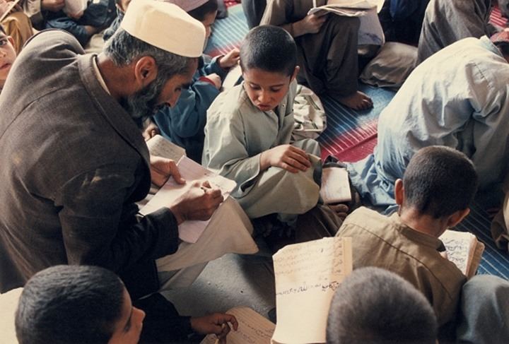 Overhead view of man studying whilst sitting among children in Afghanistan