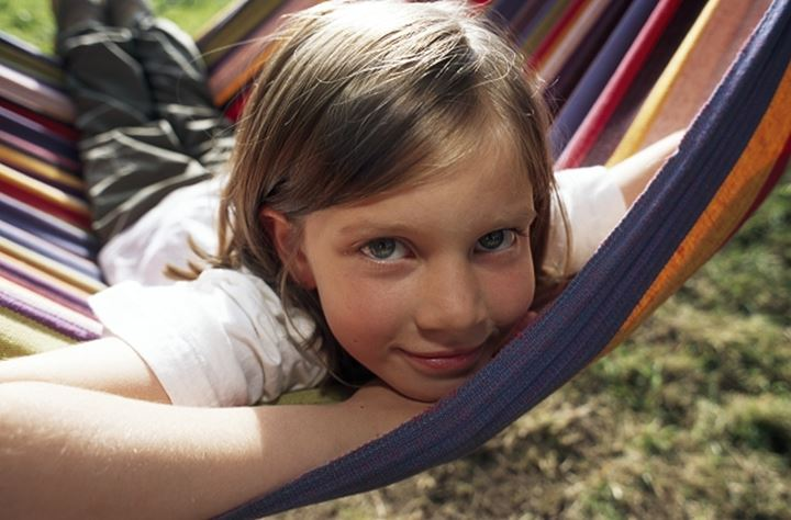 Close up view of a girl smiling and looking at camera while sitting in a swing