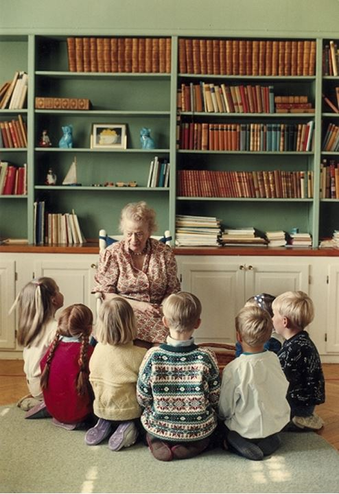 Children sitting by an old lady