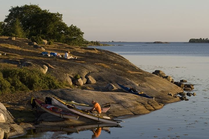 High angle view of a man sitting near kayaks at the coast, Sweden