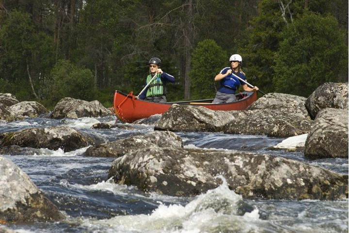 Canoeing down a rapid with lots of stones