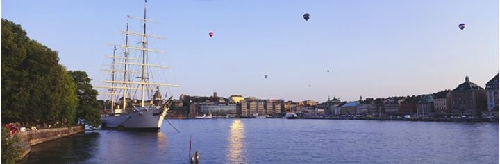 A boat by Stockholm, hot air balloons in the air