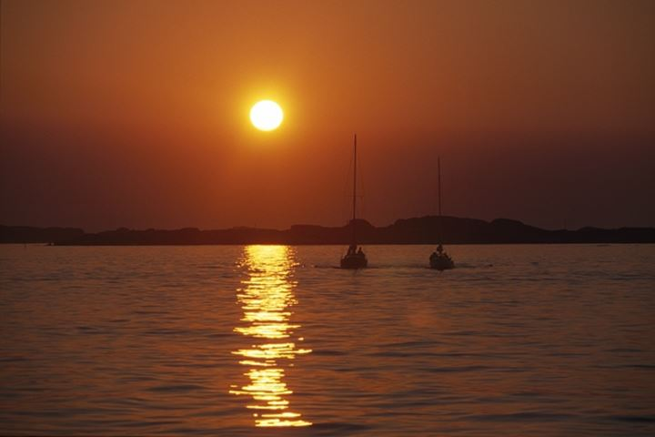 Silhouette of two sail boats sailing in the sea at sunset