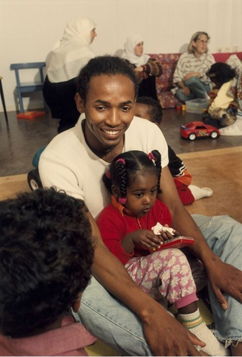 Man smiling while sitting with his daughter