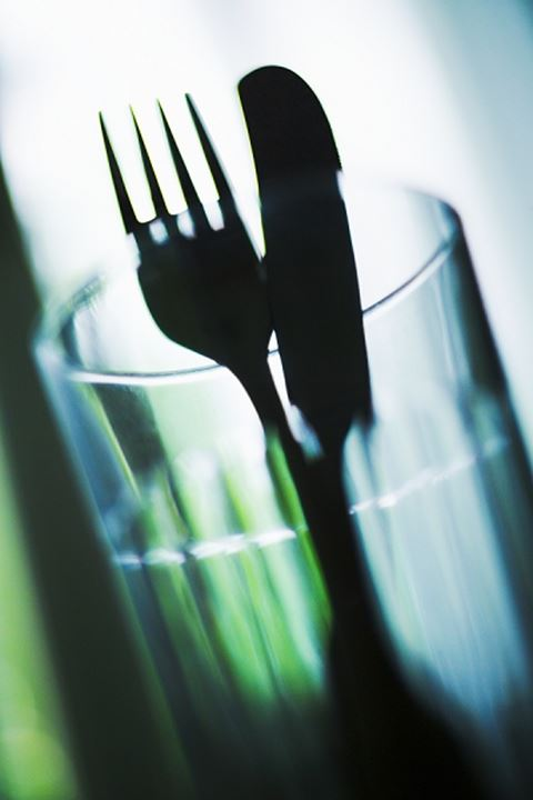 Close-up of a fork and table knife in a glass