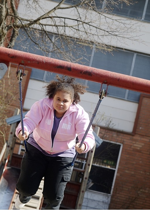 Front view of a girl swinging high on a swing