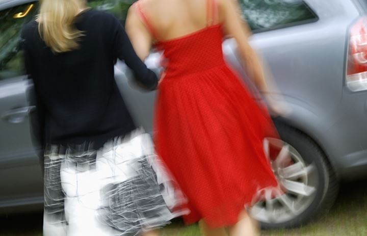 Rear view of girls standing by the car
