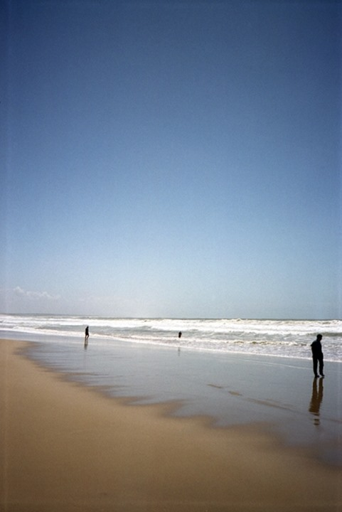Three people standing on the beach, Morocco