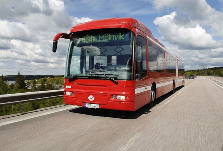 Front view of a red bus moving on the road