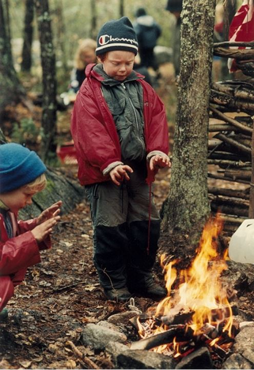 Children warming their hands by the fire