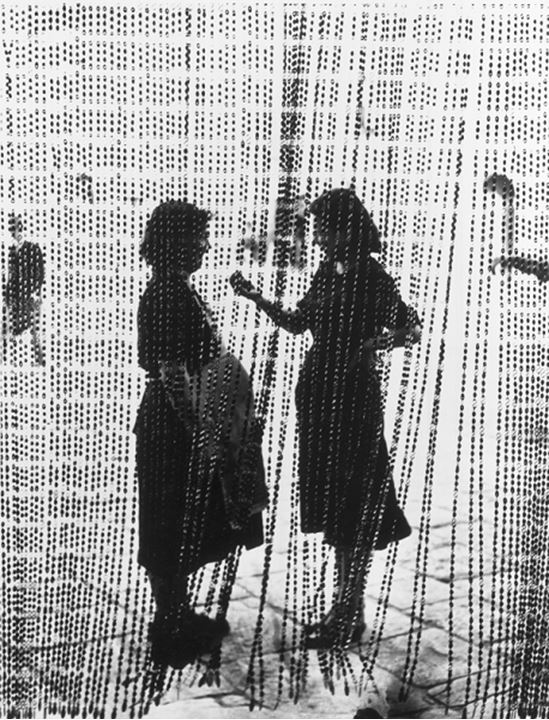 Two people standing behind the beaded curtain