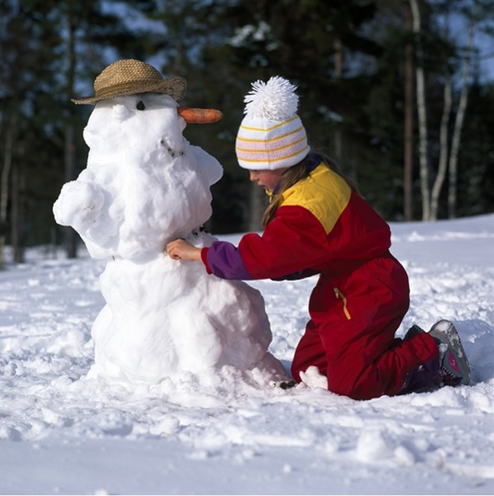 Side profile of a girl making a snowman