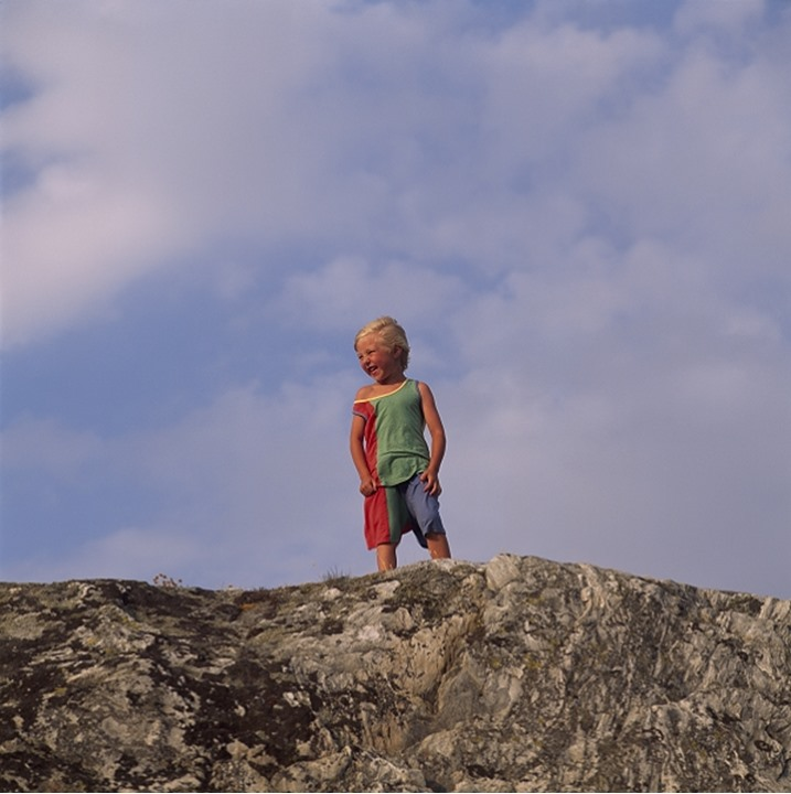 A boy standing against the cloudy sky