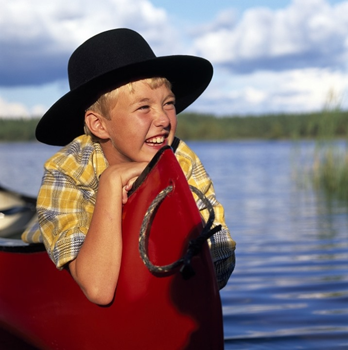 Close-up of a boy smiling, lake Jämnasjön in Västra Götaland, Sweden.