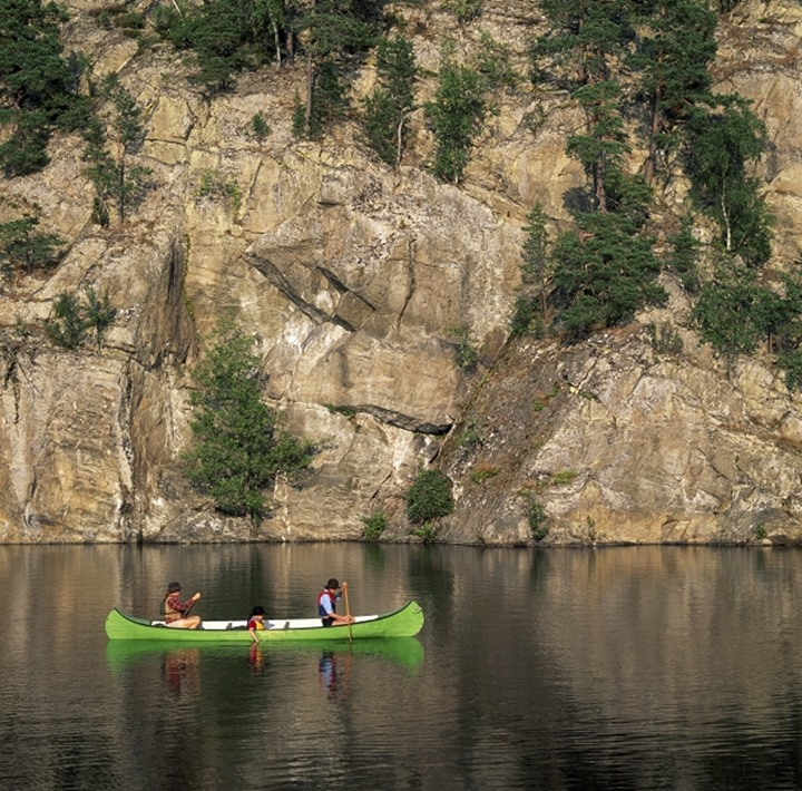 Two people boating in a lake Djup in wilderness in Dalsland, Sweden.
