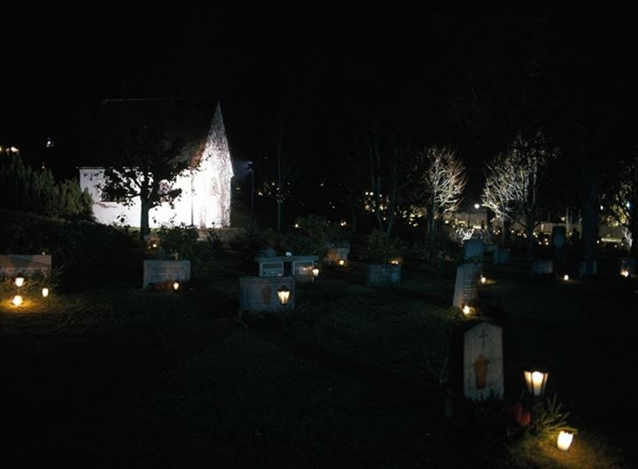 Graveyard with trees and lights at night