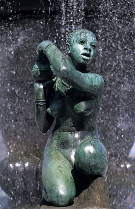 A sculpture of a woman under the waterfall