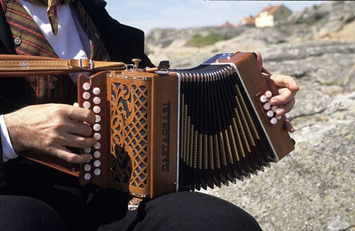 A person playing accordion outdoors