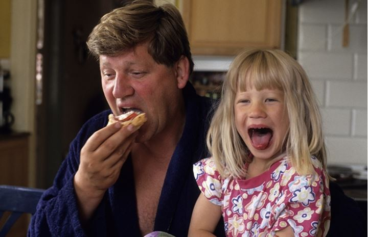 Father having breakfast with his daughter