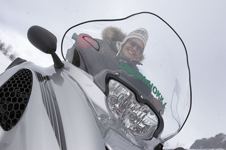 Young woman riding a snowmobile, Sweden