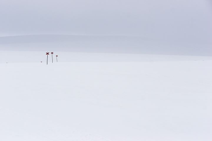 Snow covered field with windmills at a distance in Sweden