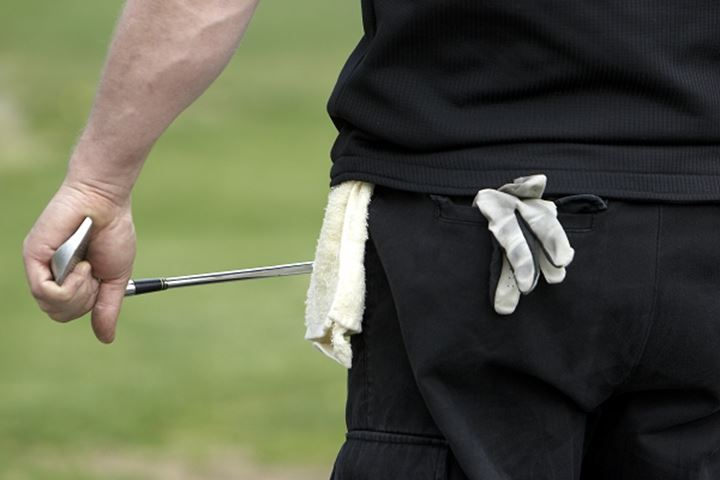 Rear view of a golfer holding golf club with glove and towel hanging out of back pocket