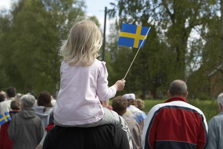 Rear view of a girl sitting on a person's shoulders and holding a Swedish flag, Sweden